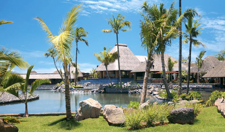 Four Seasons Mauritius exterior bungalows thatched rooves waterfront palm trees
