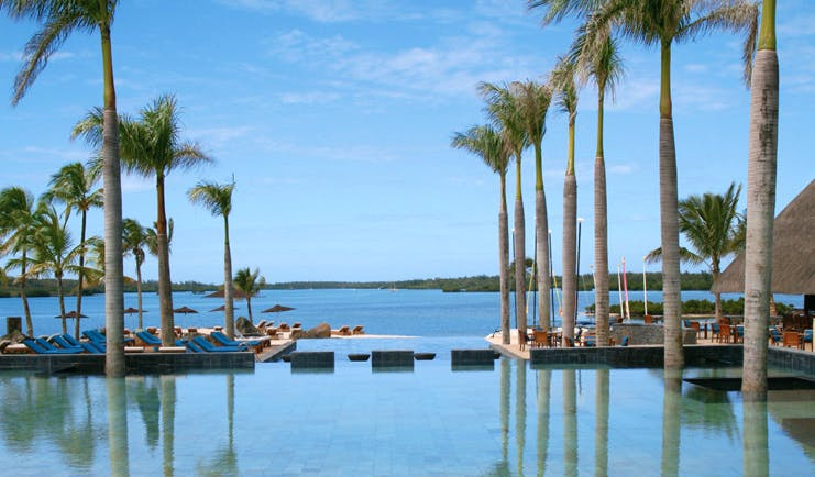 Four Seasons Mauritius infinity pool palm trees sun loungers ocean view