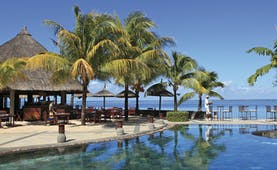 Heritage Awali Mauritius pool terrace overlooking sea palm trees