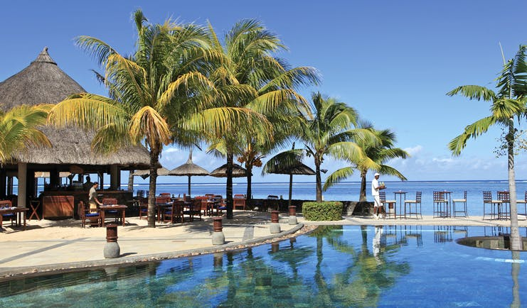 Heritage Awali Mauritius pool terrace overlooking sea palm trees