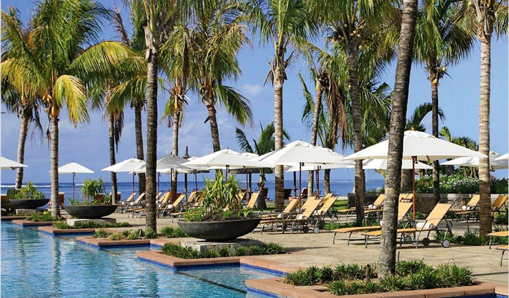 Le Telfair Mauritius poolside sun loungers umbrellas palm trees