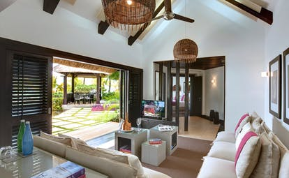 Beach front villa lounge area with sofa and doors opening onto terrace and beach