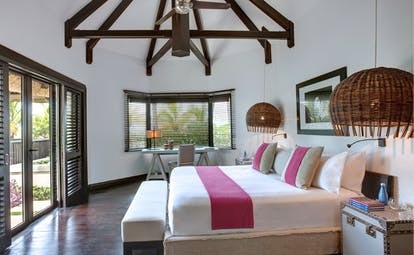 Beach front villa bedroom with large double bed and doors opening up onto beach