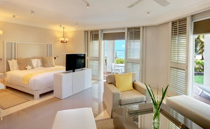 Ocean suite with television, double bed, terrace balcony and arm chairs