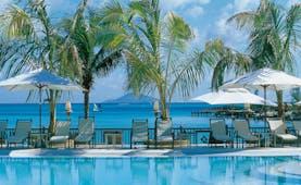 Lux Grand Gaube Mauritius poolside sun loungers umbrellas palm trees ocean in background