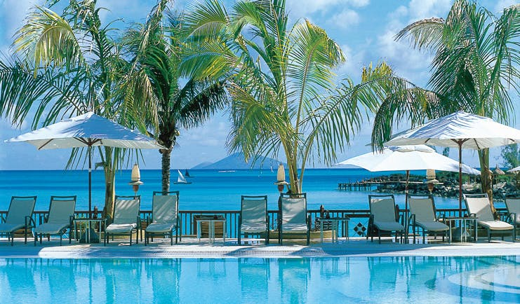 Lux Grand Gaube Mauritius poolside sun loungers umbrellas palm trees ocean in background