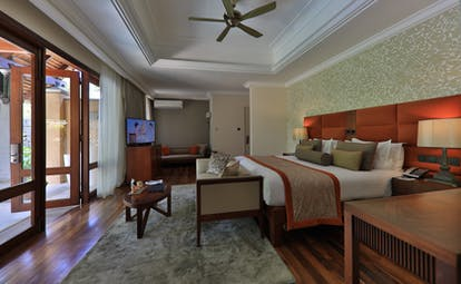 Beachfront suite pool villa bedroom with double bed and electric fan