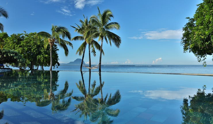 Infinity pool with palm trres reflecting in the water and ocean in the distance