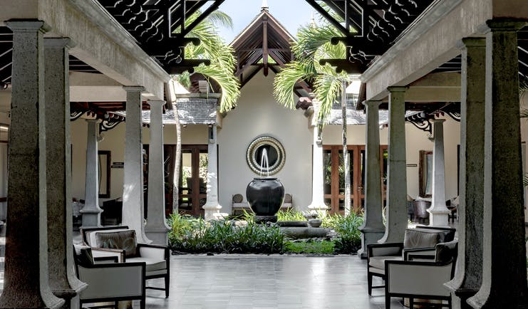 Lobby with seating areas, a water fountain and palm trees