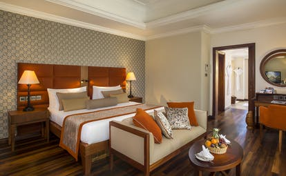 Suite interior with double bed, sofa and wood pannelled floors