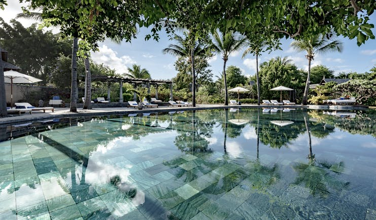 Main pool with sun loungers, umbrellas and palm trees around the outside