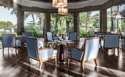 Restaurant dining area with tables and chairs set out in large wooden floored room