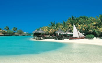 Paradise Cove Mauritius beach front palm forest thatched pavilions boat on sand