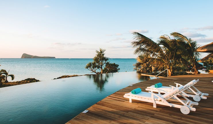 Paradise Cove infinity pool, decking, sun loungers, palm trees, overlooking sea