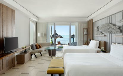 Twin room with beach access balcony, television and seating area