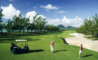Shangri La Le Touessrok Mauritius golf men playing golf mountain and ocean view