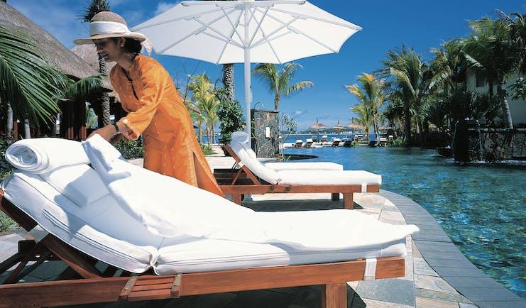 Shangri La Le Touessrok Mauritius poolside woman preparing sun lounger umbrellas palm trees