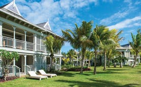 Villa exterior with villa beach style houses opening onto a grassy terrace with palm trees and sun loungers on