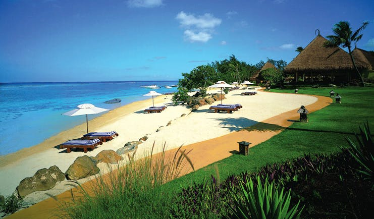 Beach with sun loungers and beach hut umbrellas near the sea