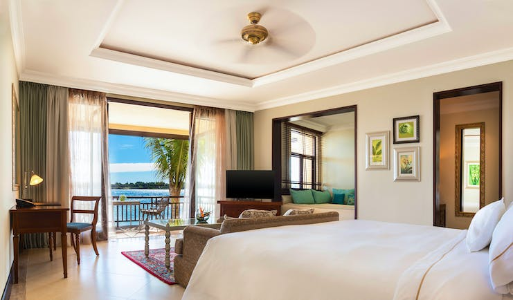 Bedroom with large double bed, electric fan, television, and double doors opening onto balcony looking over sea