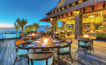 Outdoor dining terrace with candles set up on tables with palm trees and sea in backdrop