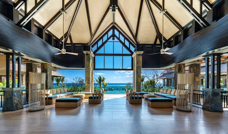 Indoor lobby with high ceilings, seating ares and space opening up over the beach