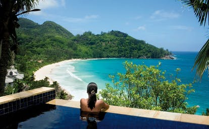 Banyan Tree Seychelles beach view pool woman looking out over beach and ocean