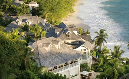 Banyan Tree Seychelles exterior aerial view of white villas in forest beach view
