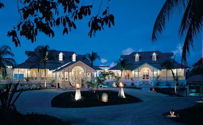Banyan Tree Seychelles exterior night white buildings lit torches