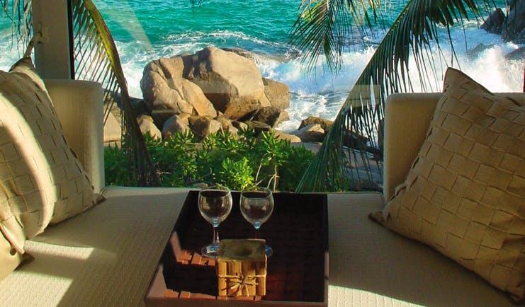 Banyan Tree Seychelles seating area sea view wine glasses ocean rocks