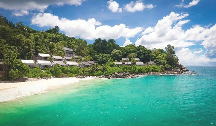 Carana Beach Hotel beach, clear turquoise sea, white sand, villas nestled in tropical greenery
