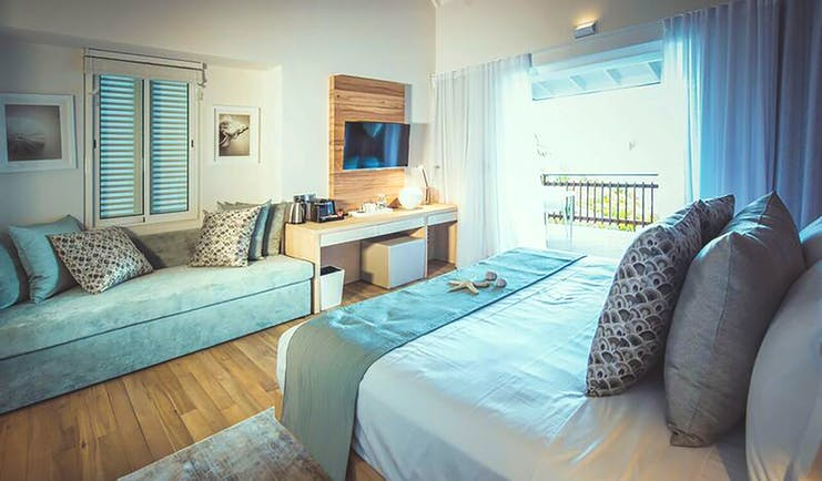 Carana Beach Hotel chalet bedroom bed, sofa, fresh modern decor, access to terrace