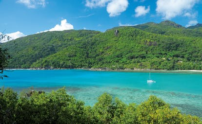 Constance Ephelia Resort Seychelles aerial view green waters tree covered mountain