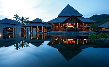 Constance Ephelia Resort Seychelles main building night time pointed rooves outdoor pool
