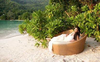 Constance Ephelia Resort Seychelles north beach woman on wicker chair greenery white sand ocean