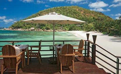 Constance Lemuria Seychelles beachfront restaurant decked dining area umbrella