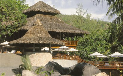 Constance Lemuria Seychelles hotel buildings thatched rooves forest view