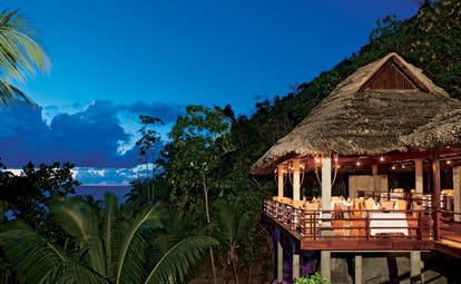 Constance Lemuria Seychelles Legend restaurant outdoor thatched pavilion palm trees night