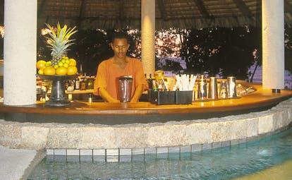 Constance Lemuria Seychelles swim up bar man mixing drinks sunset
