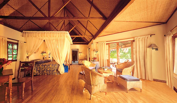 Denis Island Seychelles deluxe cottage exposed beams four poster bed lounge seating area