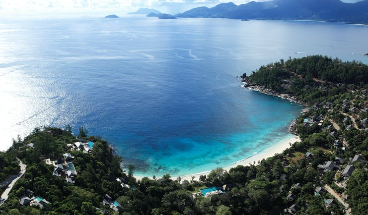 Aerial view of the beach and resort looking over the sea, beach and mountains in the distance