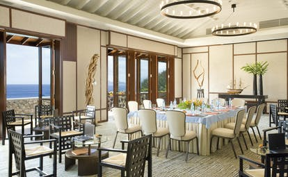 Dining area with tables and chairs set up around the room and doors opening onto an ocean view balcony