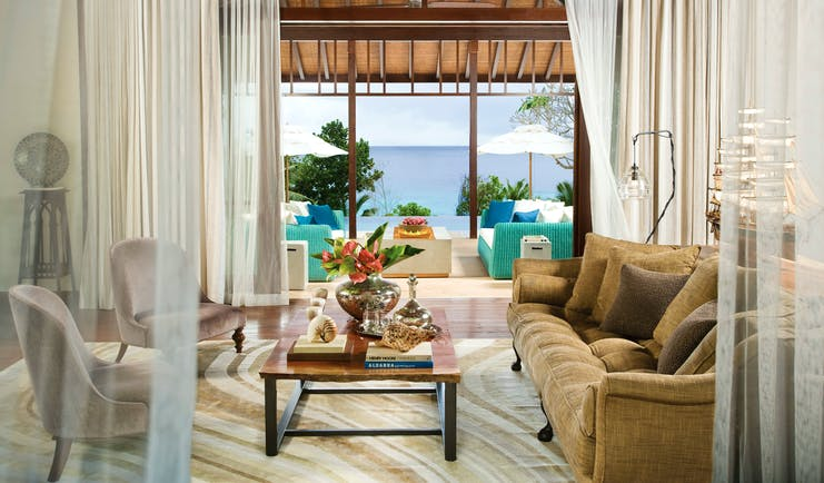 Lounge area with sofa, arm chairs and coffee table with books on and doors opening out onto a pool view