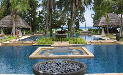 Hilton Labriz Seychelles outdoor swimming pool thatched pavilions palm trees ocean view