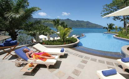 Hilton Northolme Seychelles poolside woman laying on lounger next to outdoor pool sea view