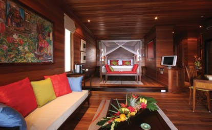 Hilton Northolme Seychelles villa interior wooden walls and floors floor poster bed sitting area tropical scene painting
