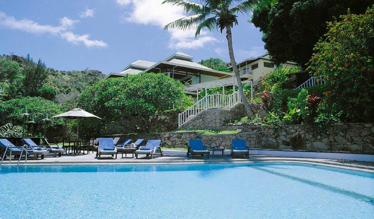 Hotel L'Archipel Seychelles outdoor pool sun loungers umbrellas