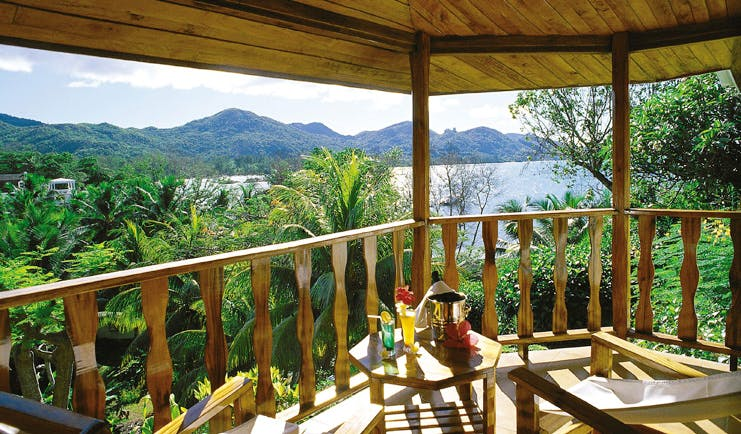 Hotel L'Archipel Seychelles covered balcony seating forest and ocean view