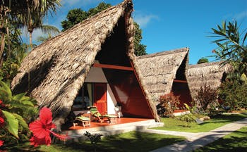 La Digue Island Lodge chalet exterior, triangle shped building, thatched roof, pathway across green lawn to front door