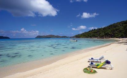 Domaine de la Reserve Seychelles aerial beach sun loungers white beach boat on waves